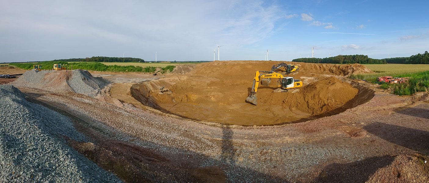 Aushubarbeiten mit zwei Kettenbaggern, hier wird eine Baugrube für das Fundament einer Windkraftanlage erstellt.
